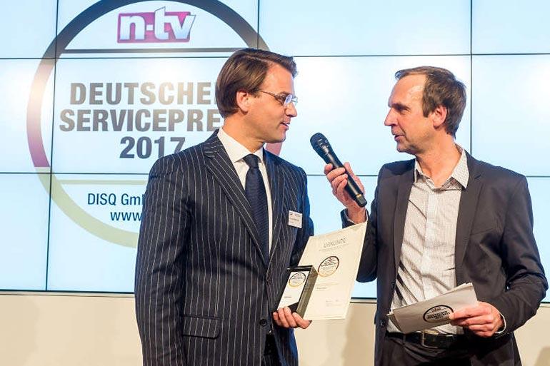 Christian Mühlhäuser, Geschäftsführer der Pneumobil Reifen und KFZ-Technik GmbH , nimmt die Auszeichnung Deutscher Servicepreis 2017 entgegen.